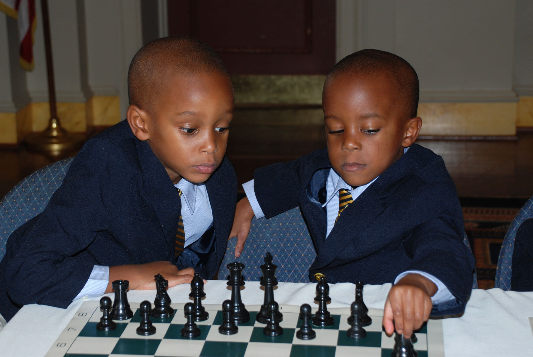 Two boys playing chess at the big chair chess club